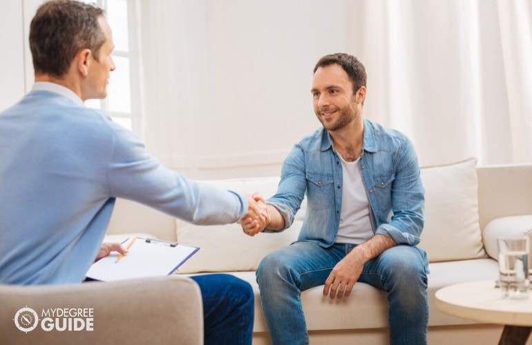 psychologist shaking hands with a patient after a therapy session