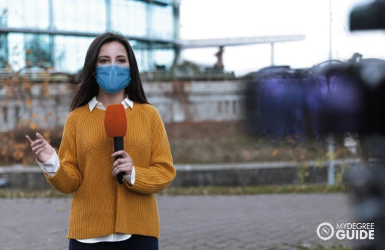 Journalist giving news while wearing a mask