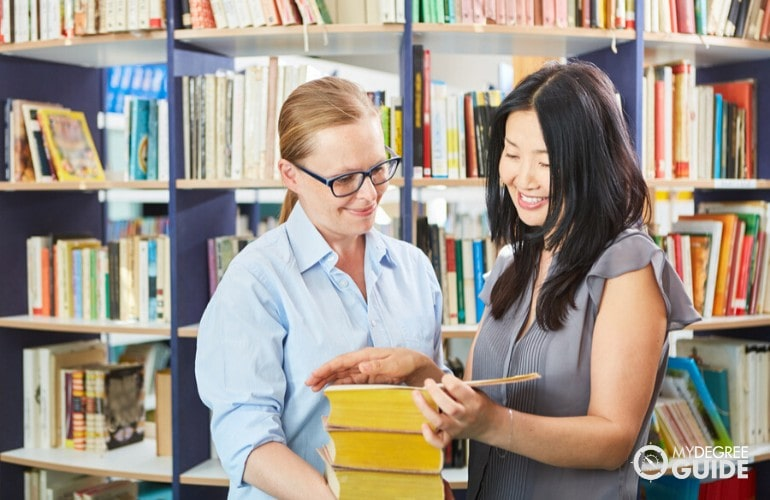 Librarian helping a student find a book