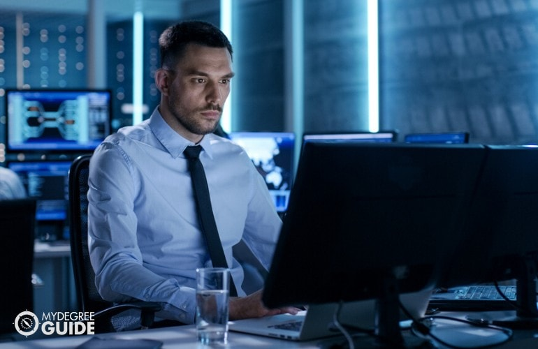 Senior Program Analyst working on his computer