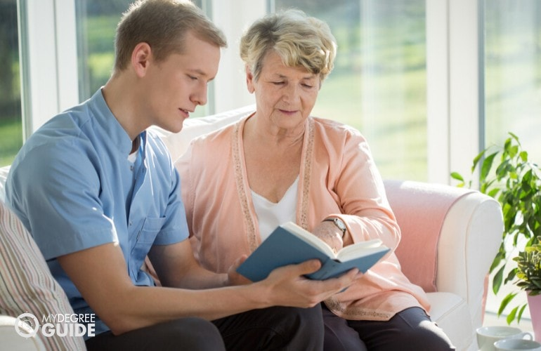 social worker helping an elderly woman in reading her book