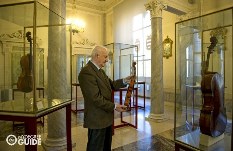 Violin Curator with his collection in a museum