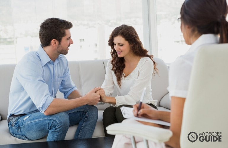 couple with a counselor in an office