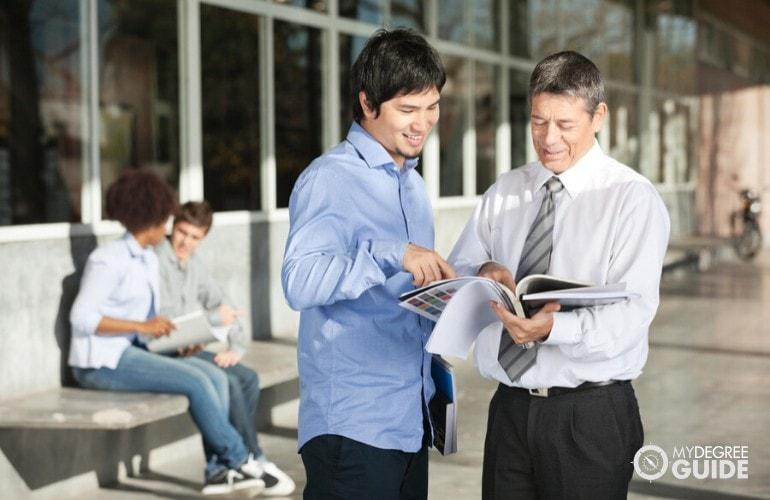 college professors talking in university hallway