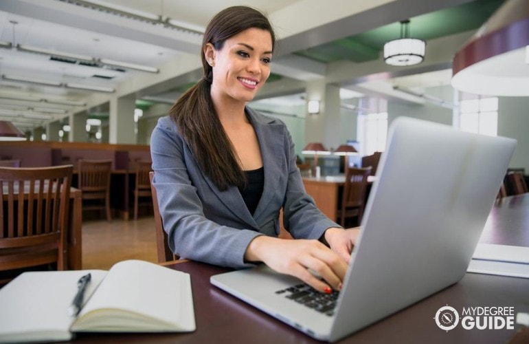 Masters in International Business student studying on her laptop in the library