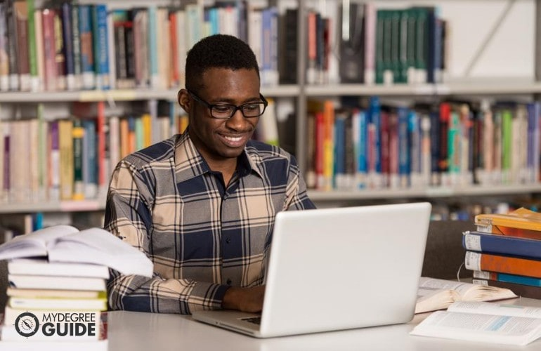 Bachelor's in Computer Engineering student studying online in a library
