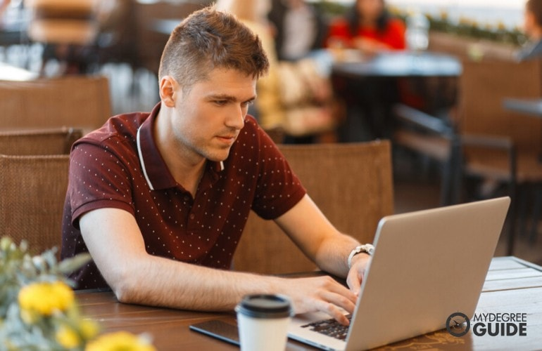 Bachelor's in Public Administration student studying on his laptop