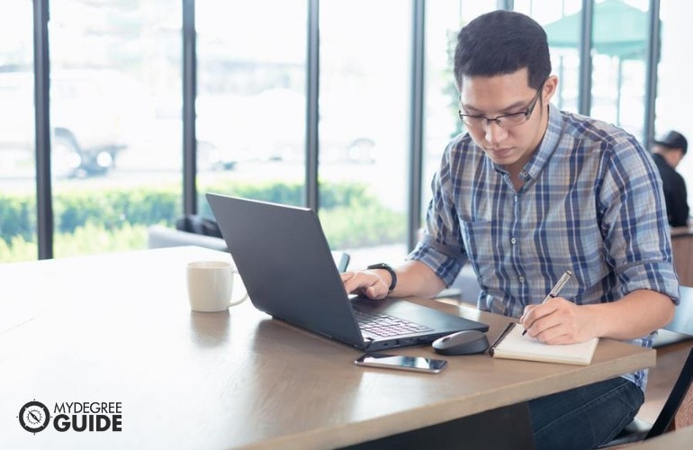 Bachelor's in Social Work Degree student studying online at a cafe