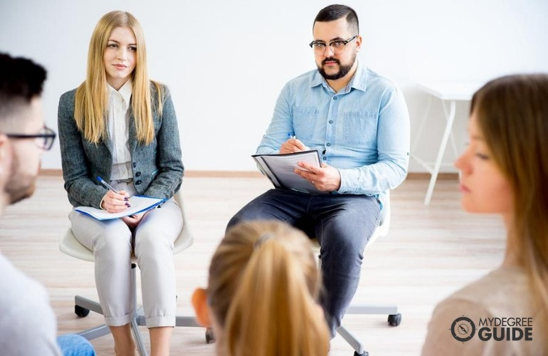 family therapists taking down notes during a counseling session with a family