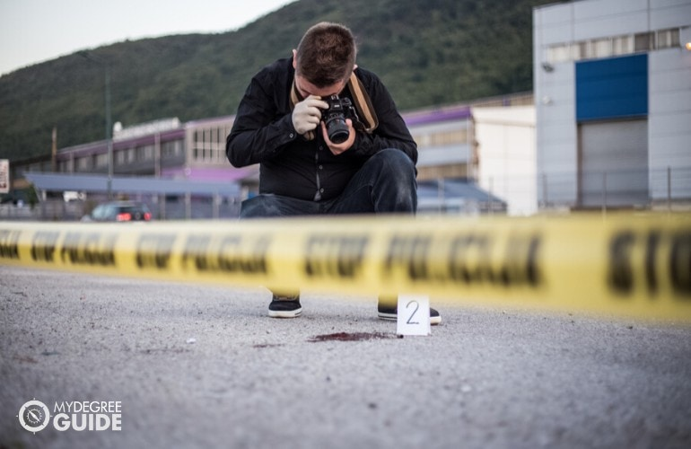 crime scene investigator taking pictures in a crime scene