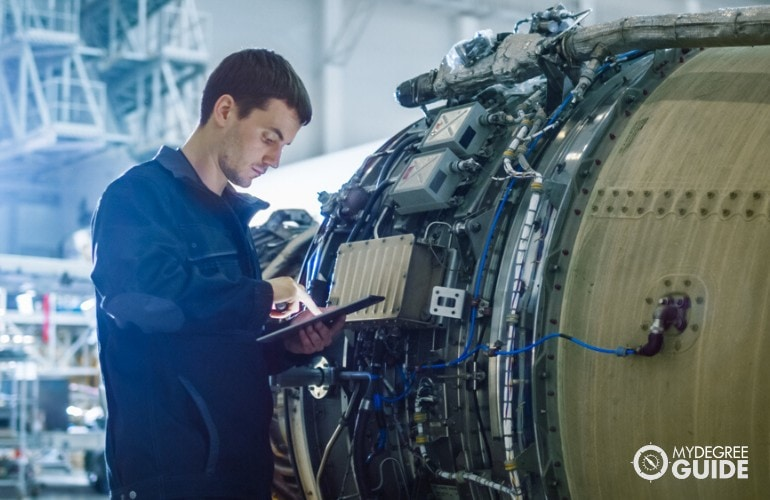 Aerospace Engineer checking the engine of an airplane