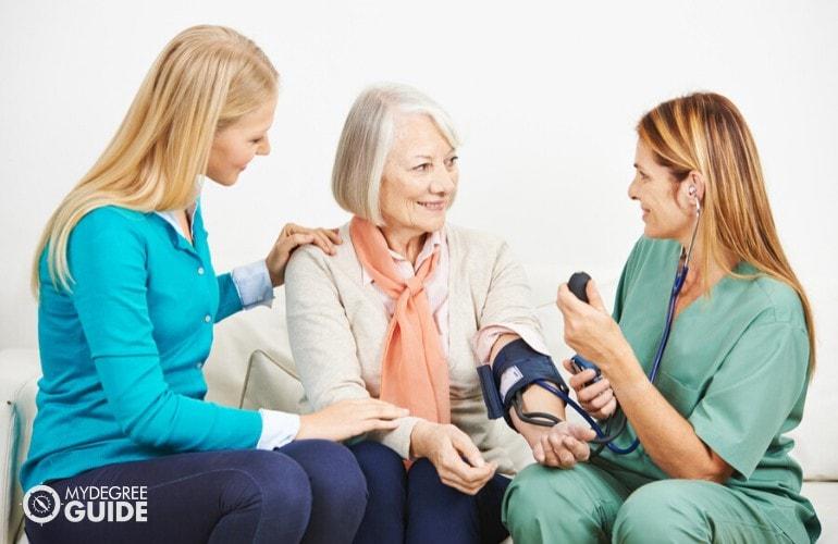 family nurse checking an elderly woman's blood pressure