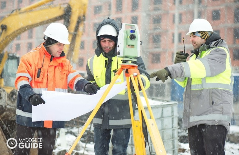 Civil Engineers working in a construction site under harsh weather