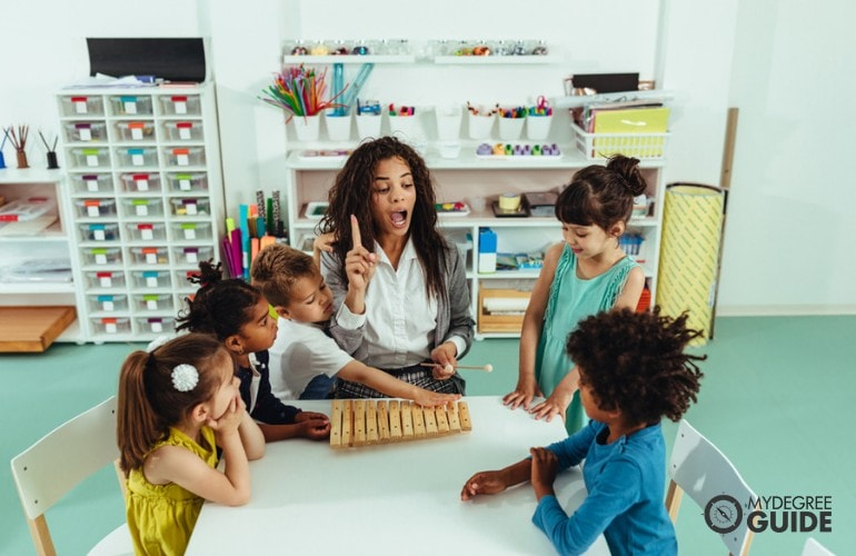 Preschool Teacher teaching her students how to play a xylophone