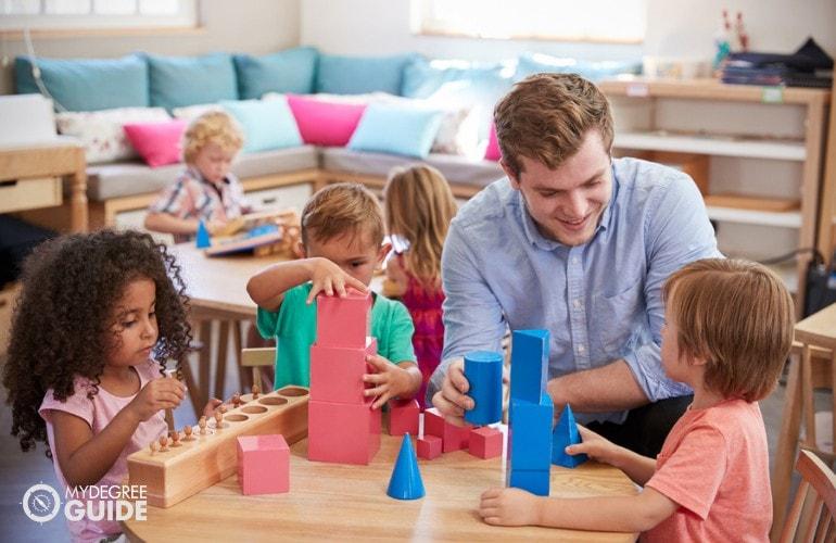 Preschool Teacher helping her students during playtime