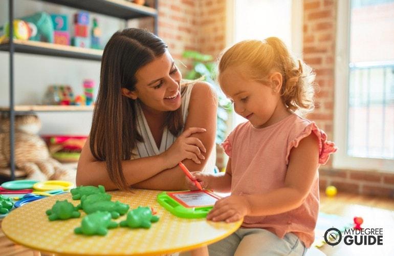 Preschool Teacher teaching a child in class