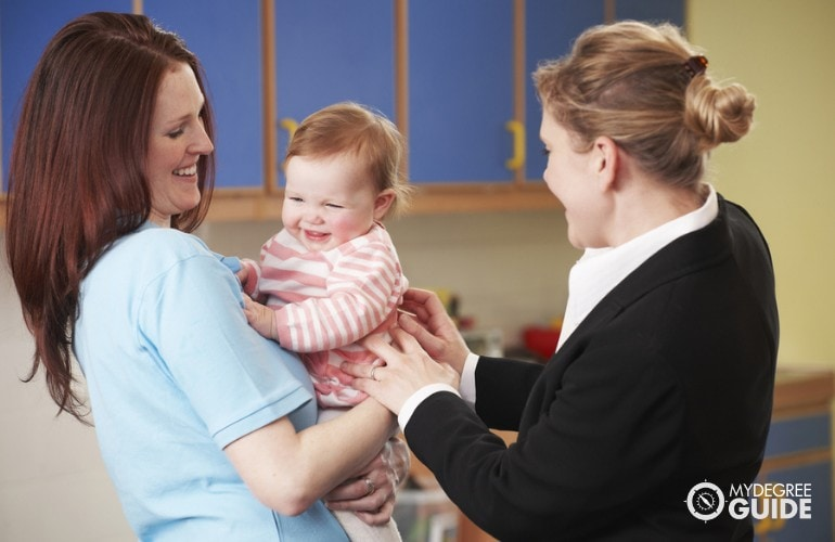 childcare worker taking care of a baby in daycare center