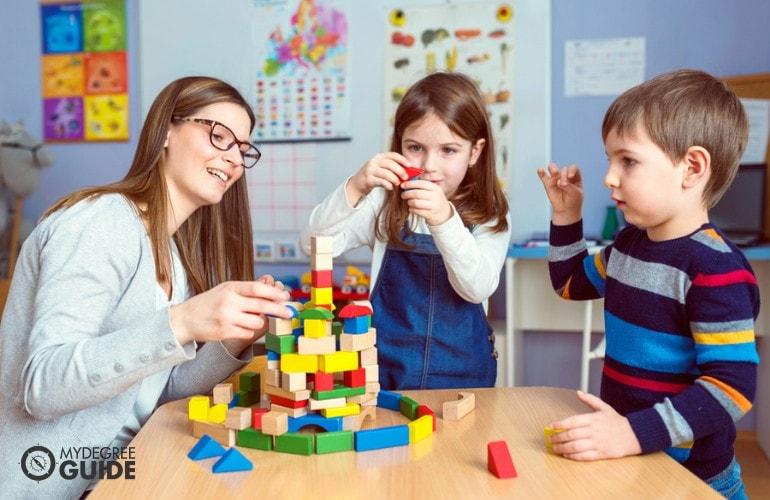 Kindergarten Teacher building blocks with her students in class