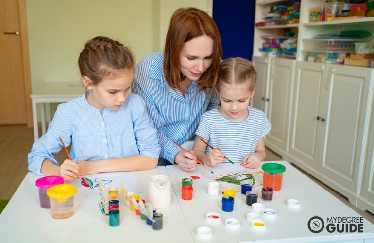 Preschool teacher helping her students in art class