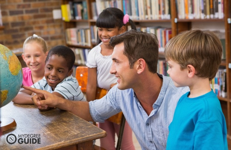 Elementary teacher with his students in library