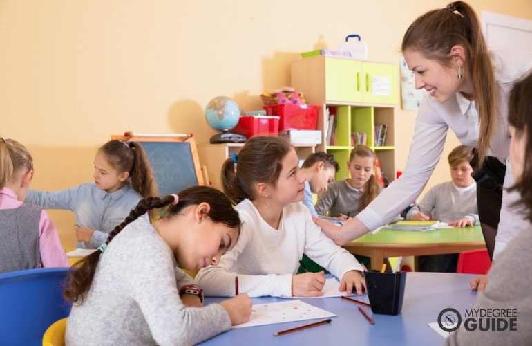 Elementary teacher checking her students during class activity