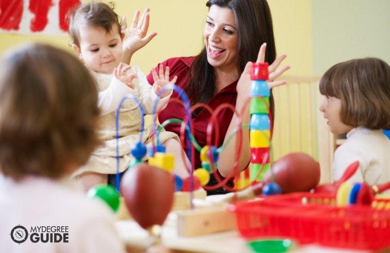 Preschool teacher happily teaching her students in class