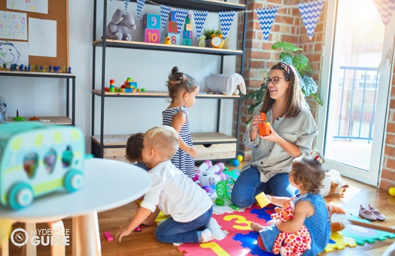 Preschool teacher playing with a group of toddlers