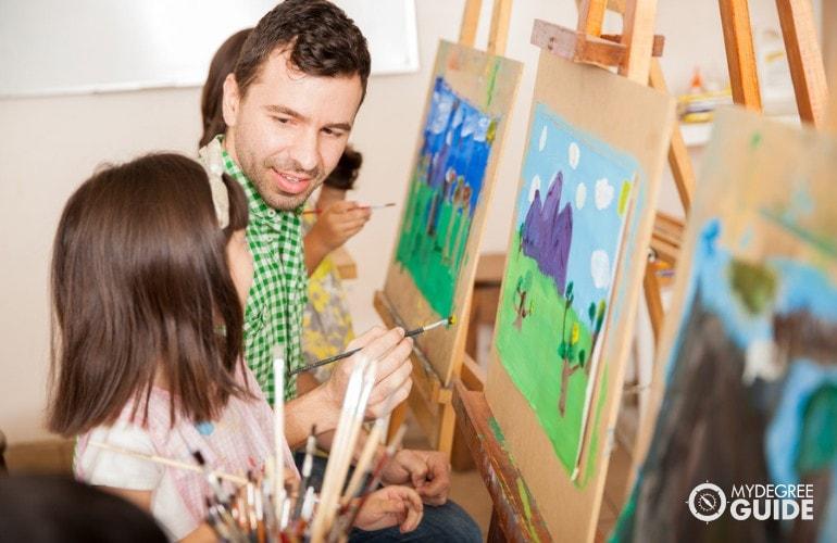 Kindergarten teacher teaching his students during art class