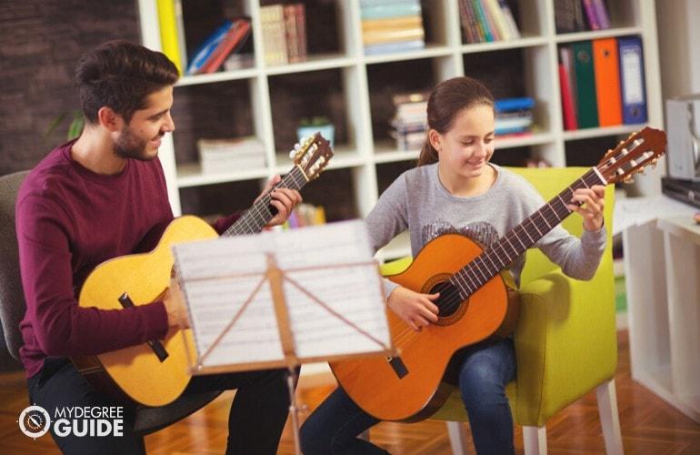Music Teacher teaching a student to play guitar