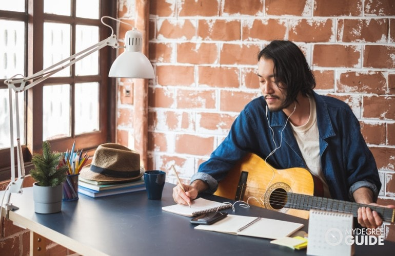 musician writing a song at home