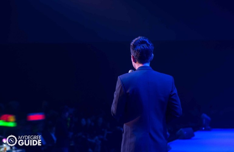 male speaker talking to international audience