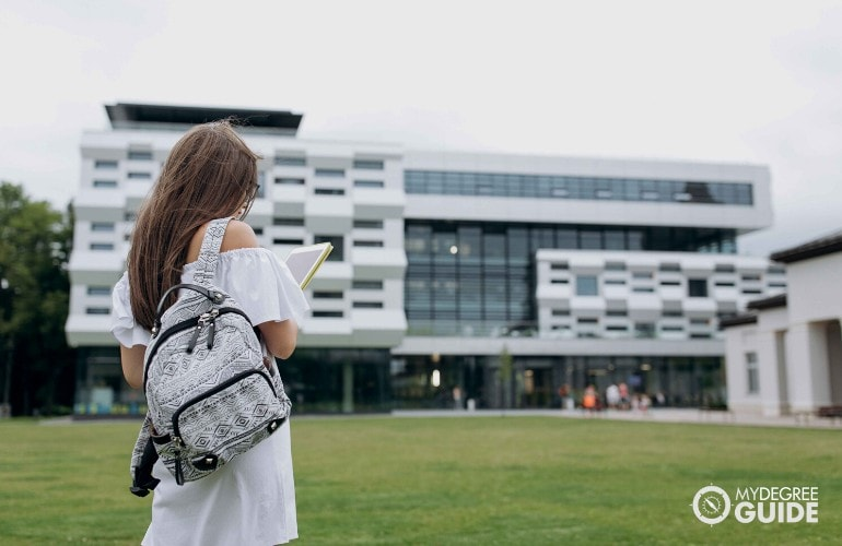female student walking into a college building
