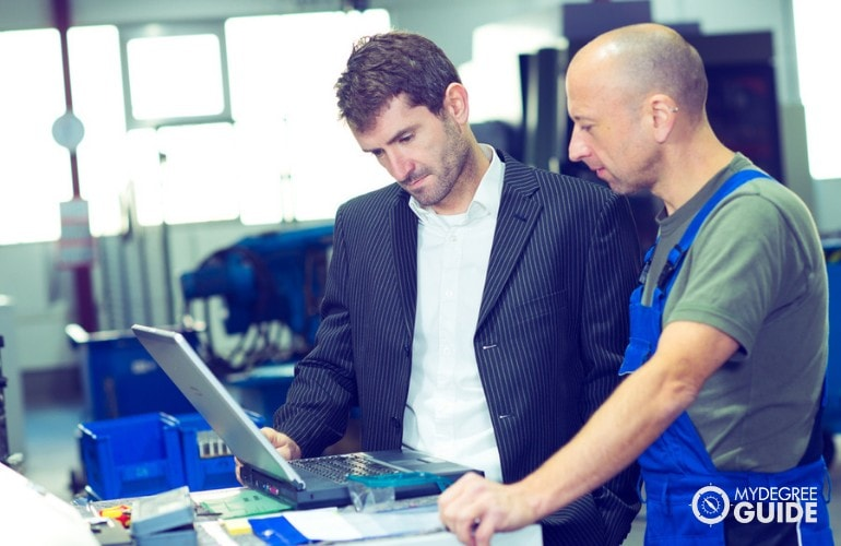 Industrial Production Manager mentoring an employee