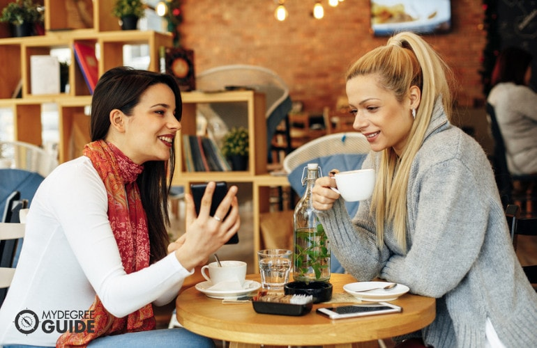 two female colleagues drinking coffee at a cafe