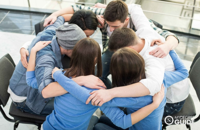 people hugging each other during group counseling