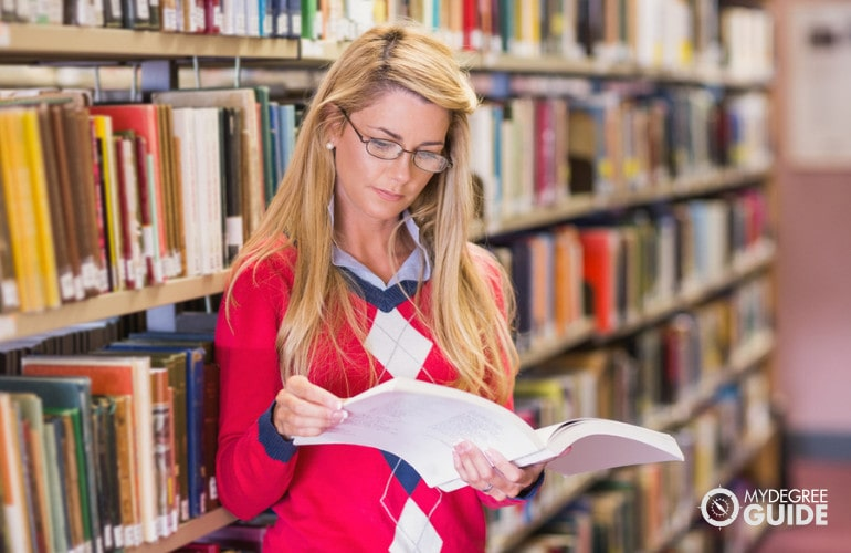 PhD in Political Science student studying in a library