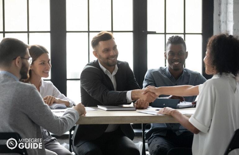 human resource managers congratulating an employee
