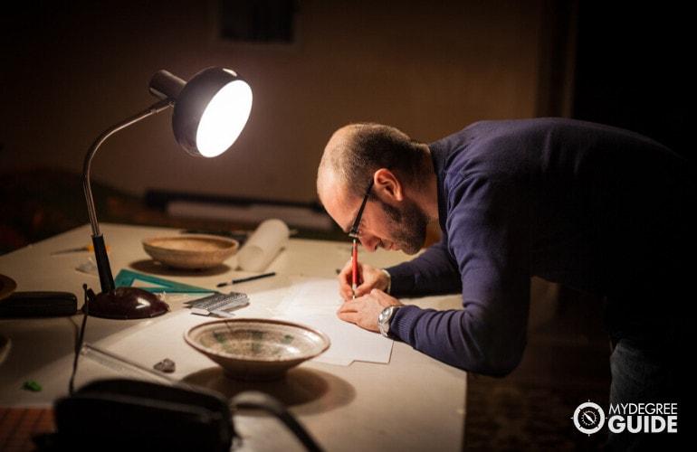 male historian examining artifacts