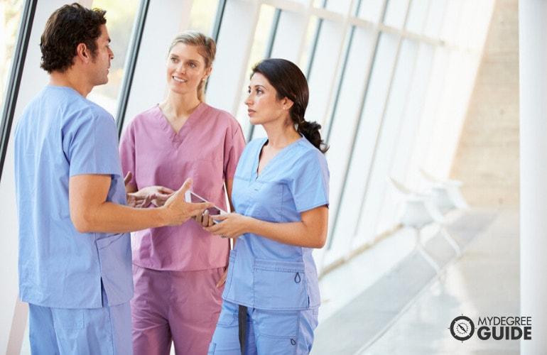 nurses meeting in hospital hallway