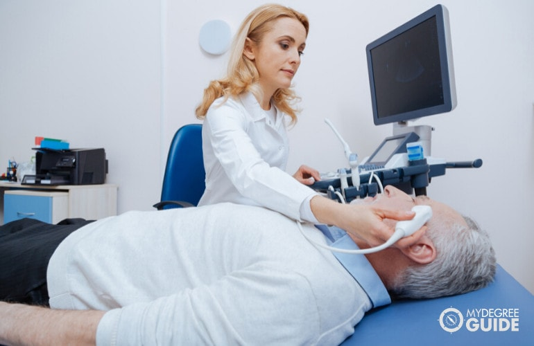 Diagnostic medical sonographer checking a patient